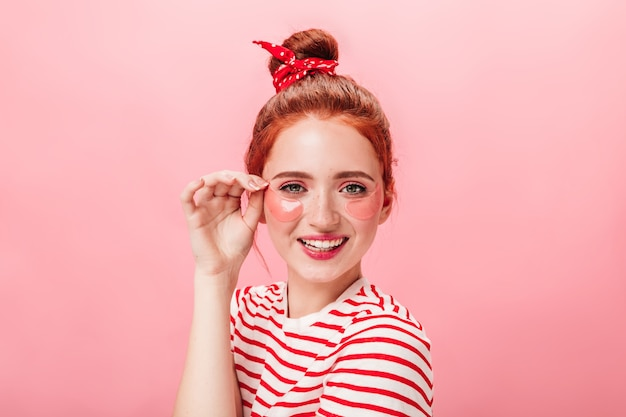 Vista frontal da menina brincalhona gengibre com tapa-olhos. foto de estúdio de jovem fazendo tratamento de pele com sorriso.