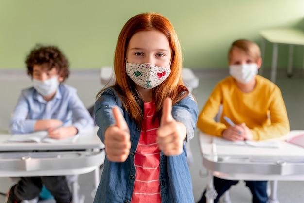 Vista frontal da menina com máscara médica na sala de aula mostrando os polegares para cima