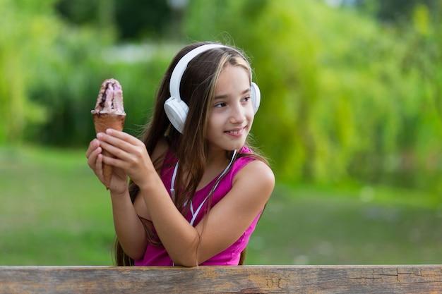 Vista frontal da menina com sorvete e fones de ouvido
