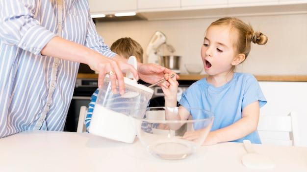 Vista frontal da menina cozinhando em casa