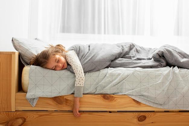 Vista frontal da menina dormindo na cama