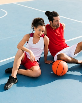 Vista frontal da menina e menino com bola de basquete