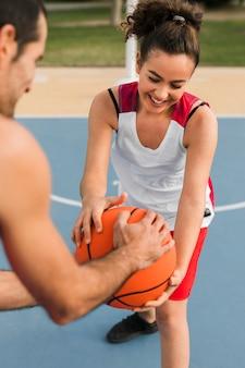 Vista frontal da menina e menino jogando basquete