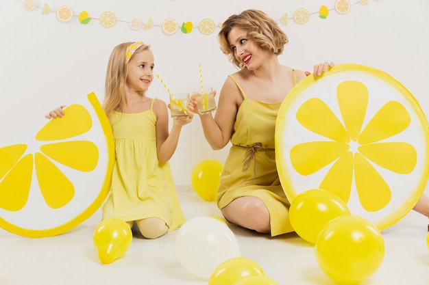 Vista frontal da menina e mulher brindando com limonada
