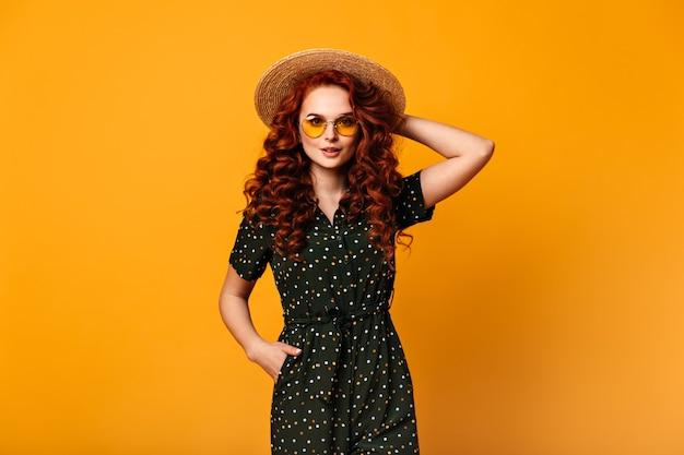 Vista frontal da menina gengibre em roupa vintage. foto de estúdio da bela jovem de óculos escuros e chapéu de palha.