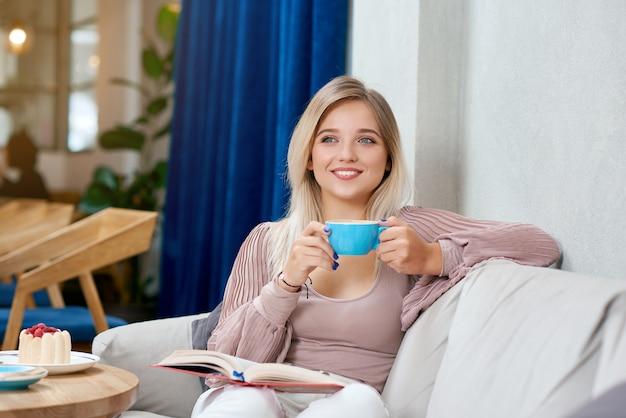 Vista frontal da menina loira sorridente, bebendo café saboroso, sentado no sofá branco.