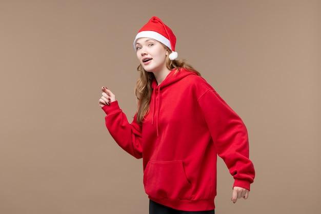 Vista frontal da menina natal no fundo marrom feriado modelo natal