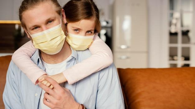 Vista frontal da menina passando um tempo com o pai usando máscara médica