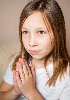 Vista frontal da menina rezando