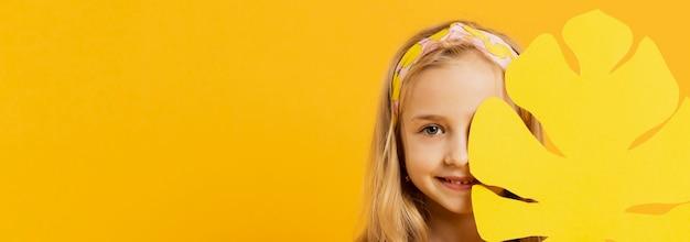 Vista frontal da menina sorridente com folha