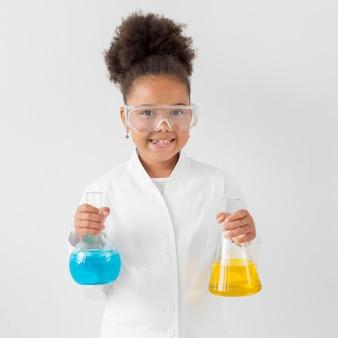 Vista frontal da menina sorridente com óculos de segurança e jaleco segurando tubos