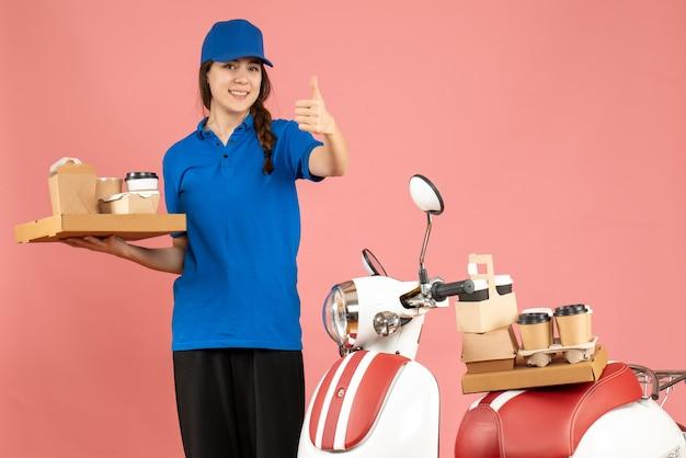 Vista frontal da mensageira ao lado da motocicleta segurando café e bolos pequenos, fazendo um gesto de ok no fundo cor de pêssego pastel