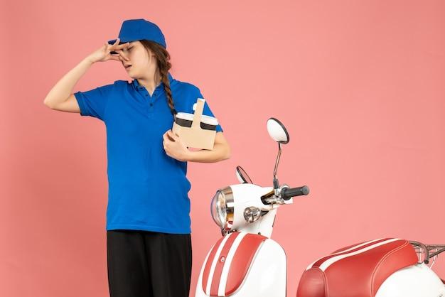 Vista frontal da mensageira ao lado de uma motocicleta segurando um gesto de café fazendo um gesto de cheiro ruim no fundo cor de pêssego pastel