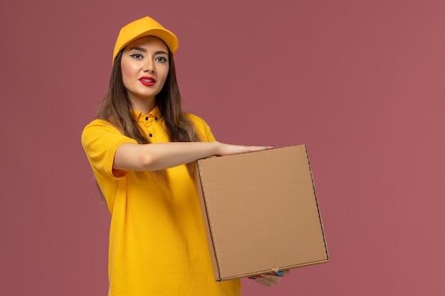 Vista frontal da mensageira de uniforme amarelo e boné segurando a caixa de comida na parede rosa claro