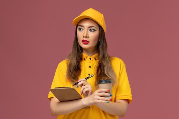 Vista frontal da mensageira de uniforme amarelo e boné segurando a xícara de café de entrega e o bloco de notas com caneta
