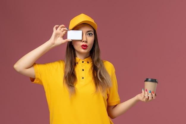 Vista frontal da mensageira de uniforme amarelo e boné segurando a xícara de café de entrega e um cartão branco