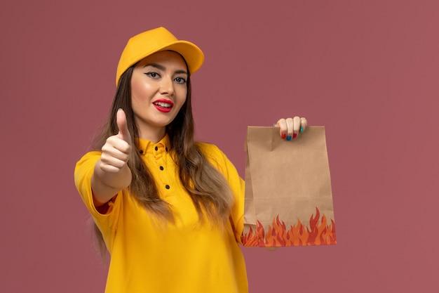 Vista frontal da mensageira de uniforme amarelo e boné segurando o pacote de alimentos na parede rosa claro