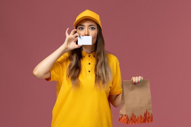 Vista frontal da mensageira de uniforme amarelo e boné segurando o pacote de comida e o cartão de plástico na parede rosa
