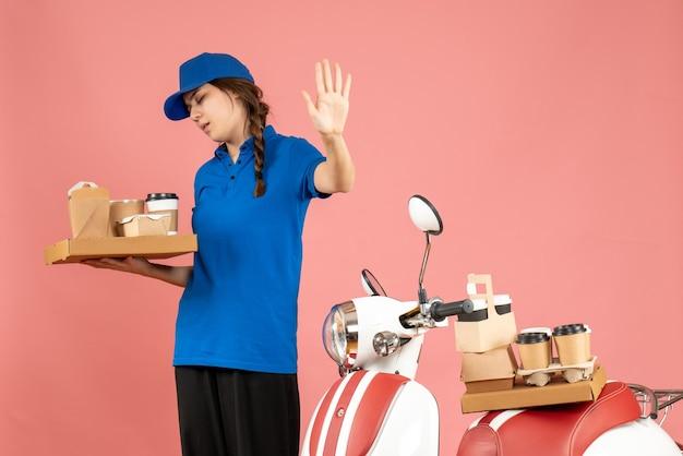Vista frontal da mensageira em pé ao lado da moto segurando café e bolos pequenos, fazendo gesto de parada no fundo cor de pêssego pastel