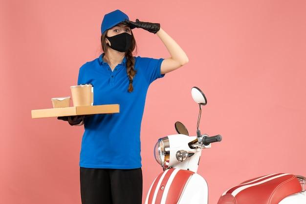 Vista frontal da mensageira usando luvas de máscara médica em pé ao lado de uma motocicleta segurando pequenos bolos de café focados em algo em um fundo de cor pastel de pêssego