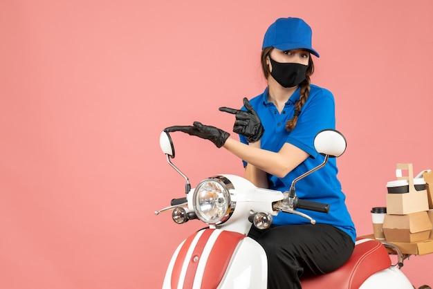 Vista frontal da mensageira usando máscara médica e luvas, sentada na scooter, entregando pedidos em fundo cor de pêssego.