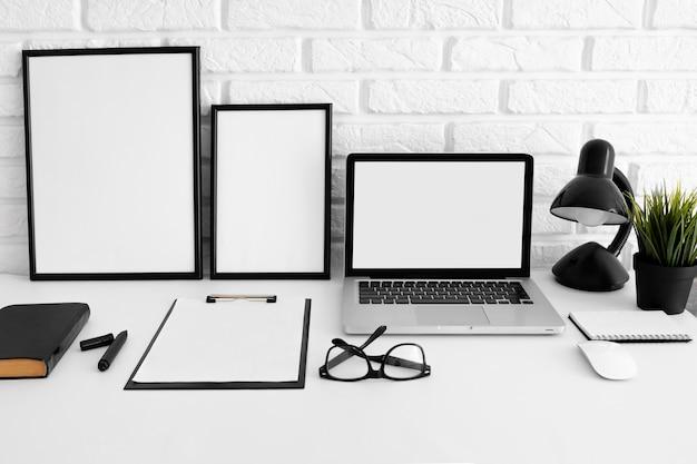 Vista frontal da mesa com laptop e óculos