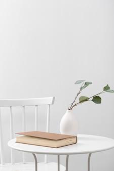 Vista frontal da mesa com livro e vaso