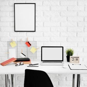 Vista frontal da mesa de escritório com laptop e cadeira