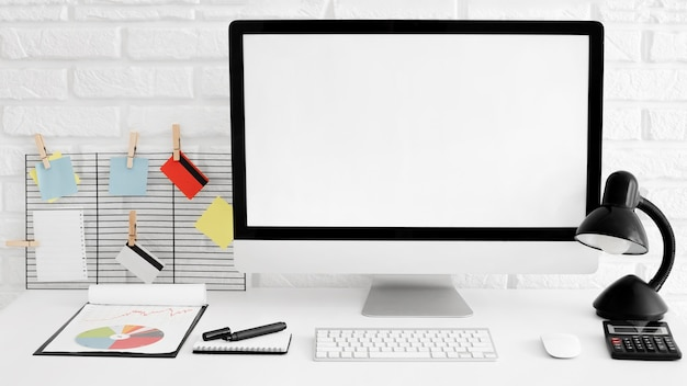 Vista frontal da mesa do escritório com computador e lâmpada