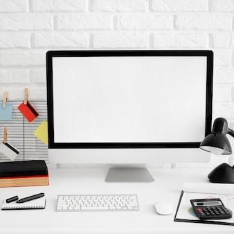 Vista frontal da mesa do escritório com tela do computador e lâmpada