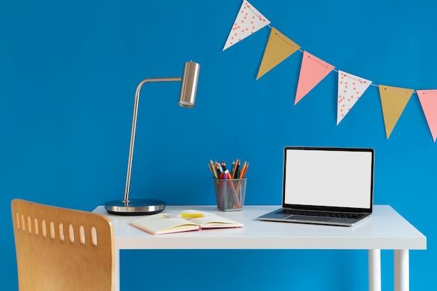 Vista frontal da mesa infantil com lápis coloridos e laptop