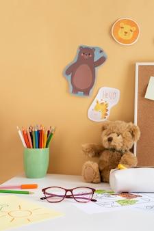 Vista frontal da mesa infantil com ursinho de pelúcia e óculos