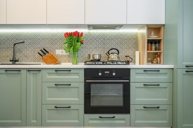 Vista frontal da mobília interior da cozinha verde moderna