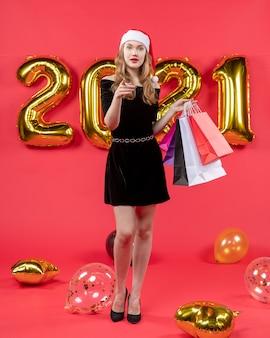 Vista frontal da moça bonita de vestido preto segurando balões de sacolas de compras em vermelho