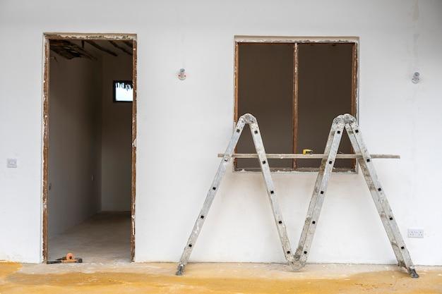 Vista frontal da moldura da janela e porta, escada e muro de concreto branco na construção incompleta da casa
