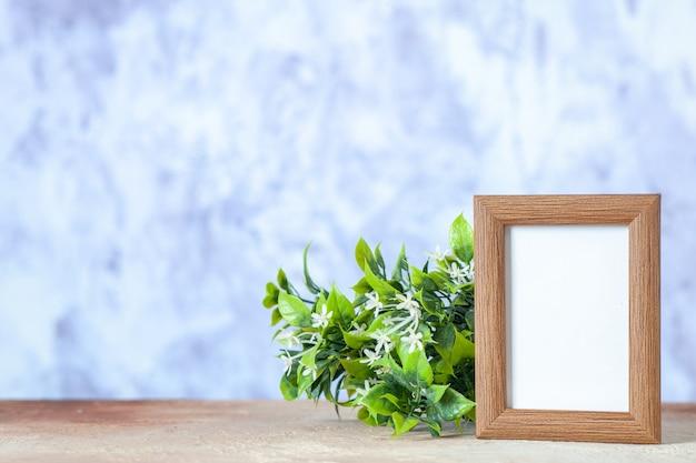 Vista frontal da moldura vazia marrom em pé sobre a mesa e a flor na superfície desfocada