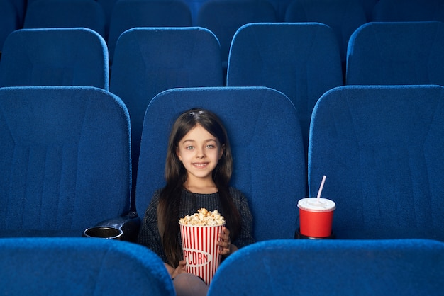 Vista frontal da morena bonita desfrutando de filme no cinema