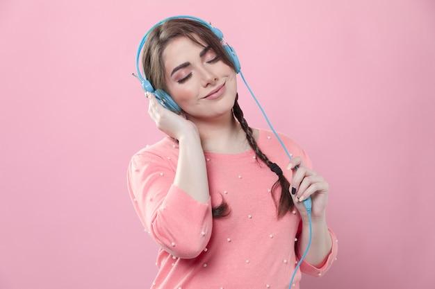 Vista frontal da mulher a gostar de música em fones de ouvido