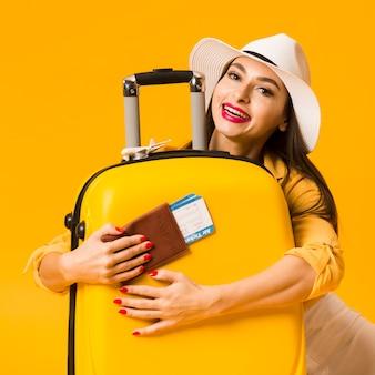 Vista frontal da mulher abraçando a bagagem e segurando o passaporte com passagens de avião