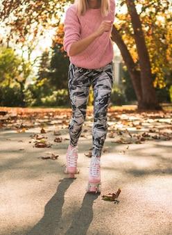 Vista frontal da mulher andar de patins com caneleiras