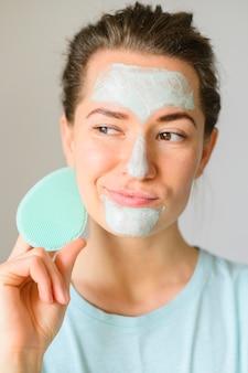 Vista frontal da mulher aplicar creme para o rosto