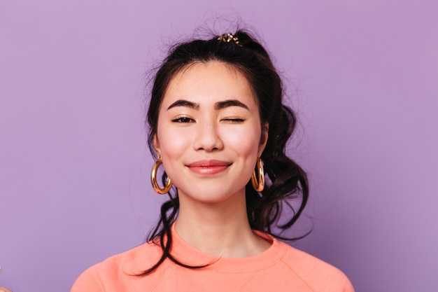 Vista frontal da mulher asiática sorridente em brincos. foto de estúdio de alegre senhora chinesa isolada em fundo roxo.