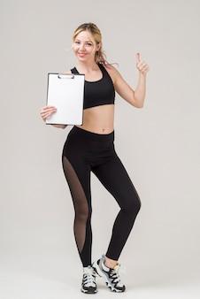 Vista frontal da mulher atlética desistindo polegares enquanto segura o bloco de notas