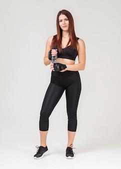 Vista frontal da mulher atlética em trajes de ginástica, segurando a garrafa de água
