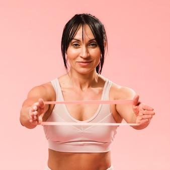 Vista frontal da mulher atlética, esticando a banda de resistência
