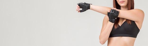 Vista frontal da mulher atlética, esticando o braço