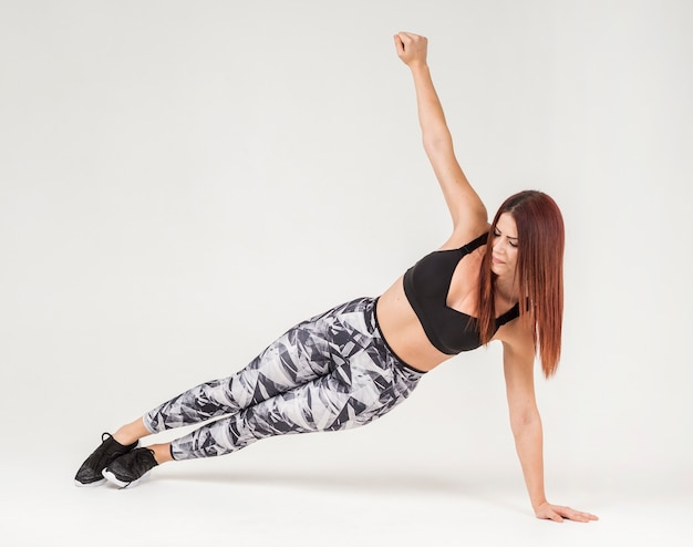 Vista frontal da mulher atlética fazendo prancha para os lados