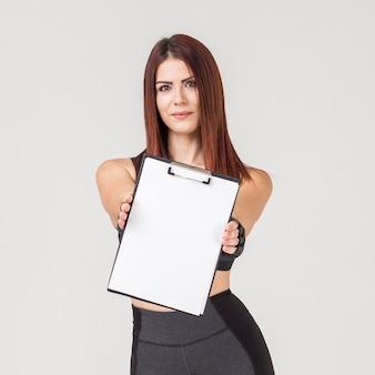 Vista frontal da mulher atlética, mostrando o bloco de notas