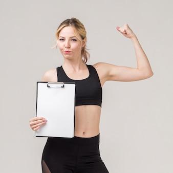 Vista frontal da mulher atlética posando ao mostrar o bíceps e segurando o bloco de notas