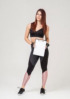 Vista frontal da mulher atlética posando enquanto segura o bloco de notas